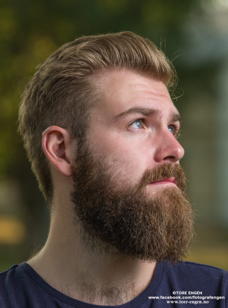Portrett av mann med skjegg som ser opp til høyre