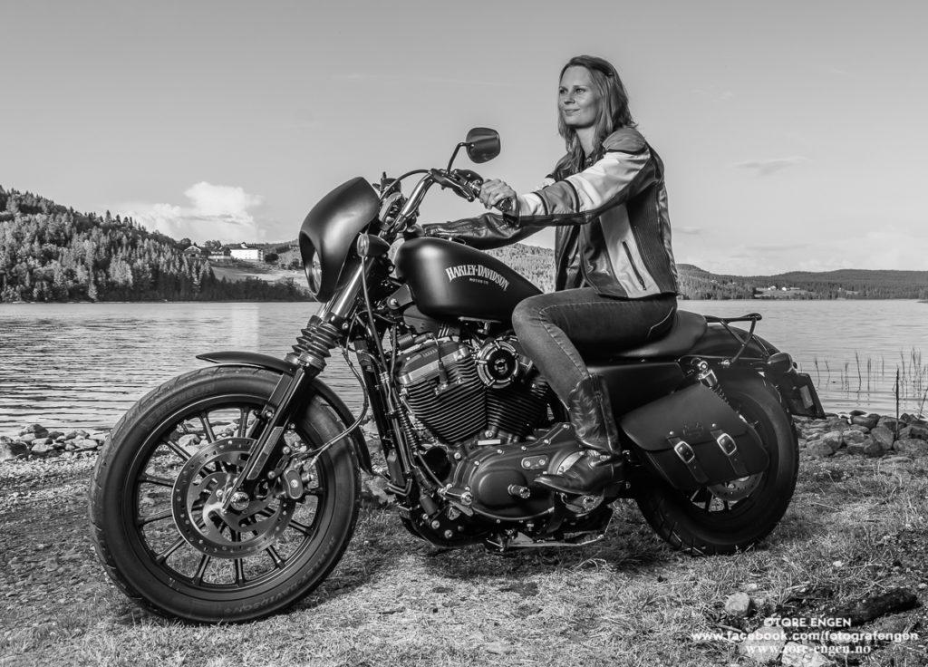 Portrett av en dame som sitter på sin Harley Davidson motorsykkel med Landåsvatnet som bakgrunn