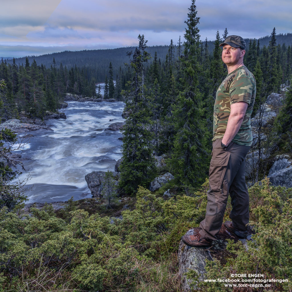 Portrett av mann i kamuflasjeklær stående ved en elv.