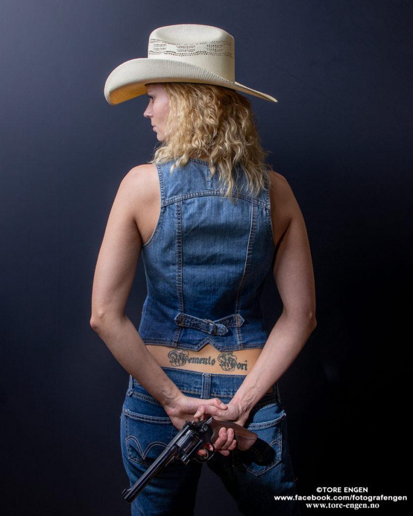 """Portrett av dame med hatt som holder en revolver bak ryggen. Hun har en tatovering hvor det står """"Memento Mori"""" nederst på ryggen."""