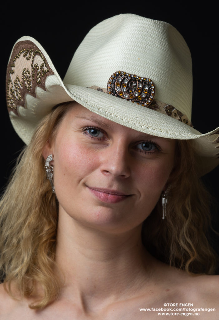Portrett av vakker dame med cowboyhatt og revolver-ørepynt
