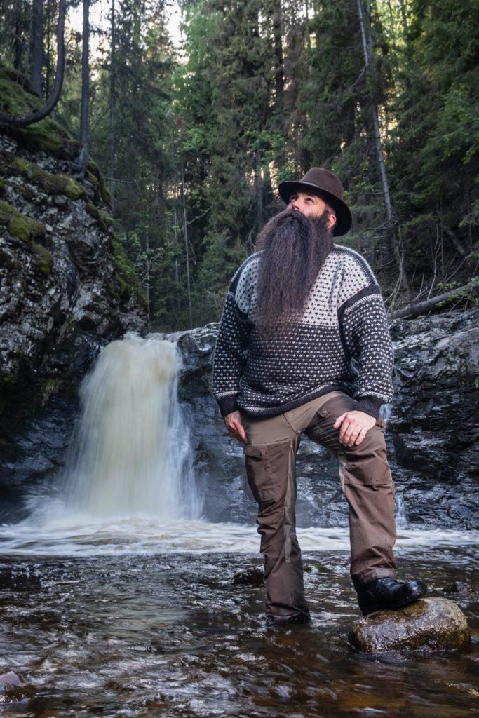 Mann med skjegg stående ved en foss i en elv