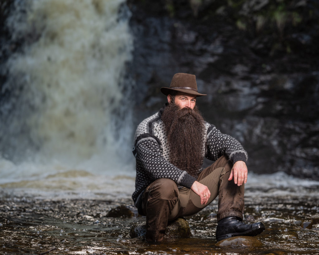 Mann med skjegg sittende ved en elv