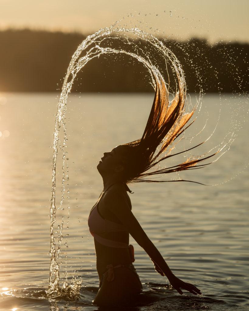 Dame som kaster vann med håret i silhuett