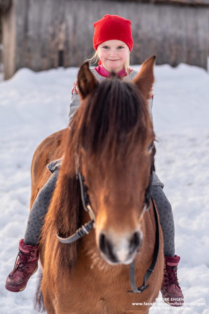 Søt lita nissejente med rød lue sittende på hest