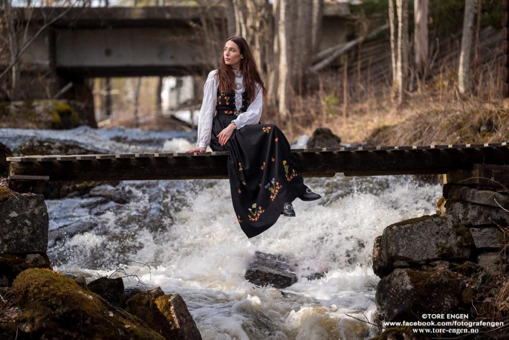 Portrett av Angie i bunad sittende på en bro over en brusende elv